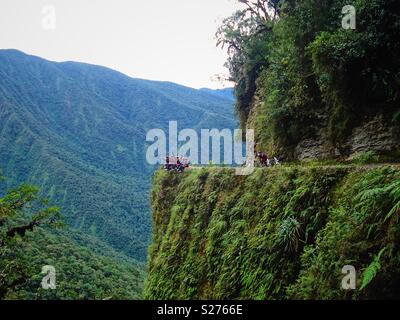 Tourists cycling down the death road in Bolivia stop and dangle their legs over the cliff with bicycles - Stock Photo