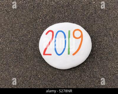 2019 year carved and painted on a stone over black volcanic sand - Stock Photo