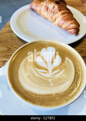 Starbucks flat white coffee with a croissant in the background - Stock Photo