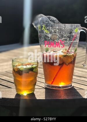 Jug and glass of Pimms, outside on garden table in sunshine. - Stock Photo