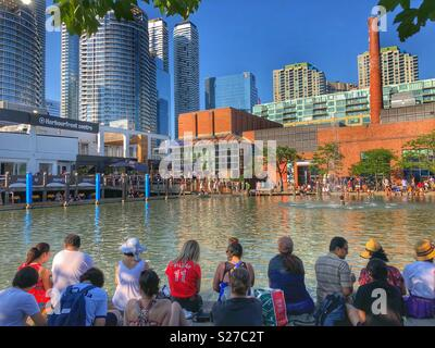 People sitting around the Natrel pond at Harbourfront Centre on a hot summer day in Toronto. - Stock Photo