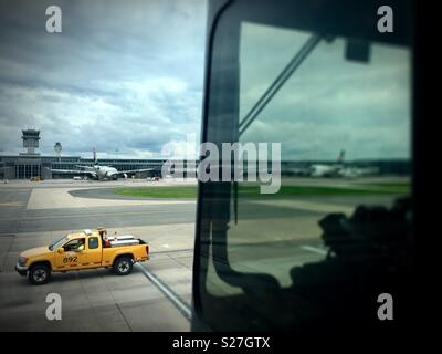Sterling, Virginia, USA - June 27, 2018: A ground vehicle passes by a mobile passenger lounge taking airline passengers to a midfield terminal at Washington Dulles International Airport. - Stock Photo