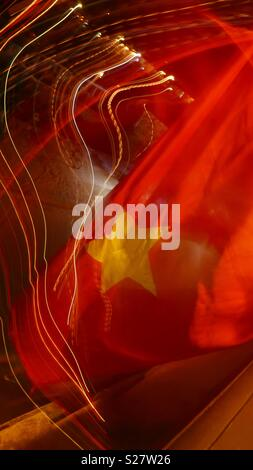 Night time abstract of street scene and Vietnamese flag taken in Hoi An, Vietnam. - Stock Photo