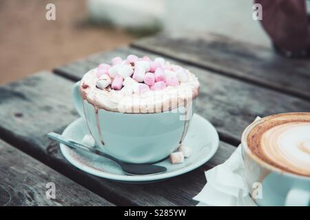 A luxurious hot chocolate drink in a cup and saucer with whipped cream and marshmallows outdoors - Stock Photo