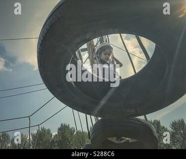 Girl on a tree top obstacle course wearing safety gear. - Stock Photo