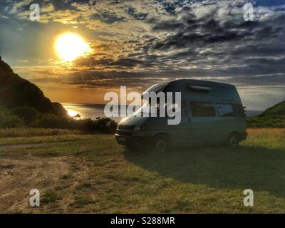 VW Camper Van parked by the sea at sunset in Lee Bay North Devon Exmoor National Park - Stock Photo