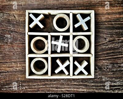 Wooden Noughts and Crosses or Tic-Tac-Toe game on wooden tabletop; crosses win. - Stock Photo