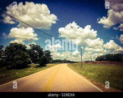 Fluffy white cumulus clouds in summer sky over rural North Carolina fields and road - Stock Photo