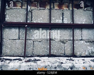 Metal framed window bricked up with concrete blocks and clay bricks - Stock Photo