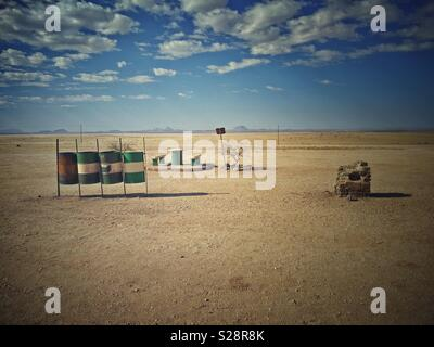 Namibian roadside rest area with seating and oil drums for recycling bins. Vintage look. Horizontal landscape format. - Stock Photo
