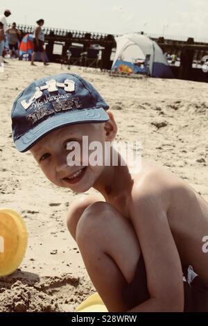 Boy wearing cap on sandy beach - Stock Photo