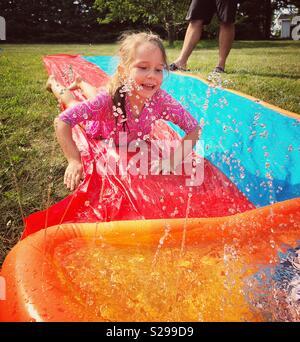 6 year old girl sliding down plastic water sprinkler slide toy outside - Stock Photo