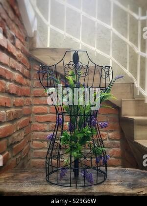 A floral display within the wire frame of a dressmaker's torso on a wooden table at the foot of a stairway with white banisters made of wrought iron - Stock Photo