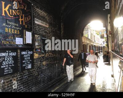 People walking down Kings Head Yard in London, England - Stock Photo