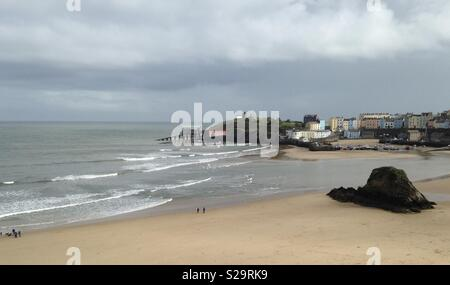 A view of Tenby North Beach and harbour showing the old and new lifeboat stations, Castle Hill, and part of the town and Goscar Rock - Stock Photo