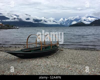 Pianello del Lario, Italy: Typical boat called 'Lucia' moored on the beach during a cloudy afternoon - Stock Photo