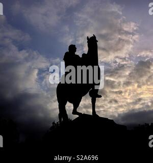 An equestrian statue of William III in Queen Square, Bristol, UK silhouetted against dramatic clouds at sunset - Stock Photo