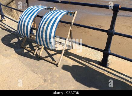 Two blue and white striped deckchairs on a windy promenade - Stock Photo