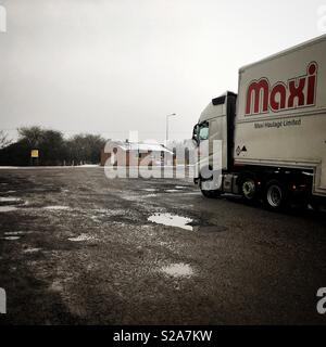Articulated lorry parked up at UK truck stop in winter. - Stock Photo
