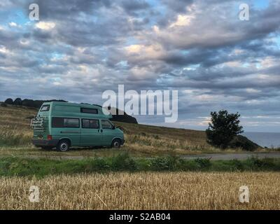 VW T4 Camper van parked by a wheat field by the North Sea - Stock Photo