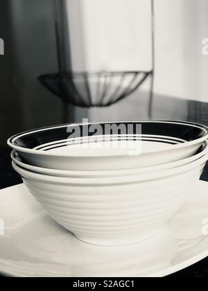 White and black classy dishes stacked on the kitchen counter top - wrought iron basket as the backdrop - Stock Photo