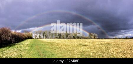 Panoramic photograph of a double rainbow above a field in the Cotswolds against grey rain clouds - Stock Photo