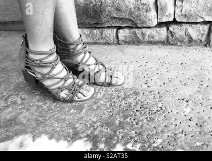 Black and white photo of a woman wearing wedged heel brown gladiator sandals with straps , standing outside on the patio next to a cobblestone wall on a summers day.