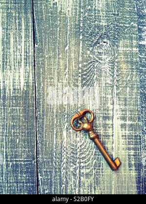 Old vintage metal key over a distressed wooden background - Stock Photo