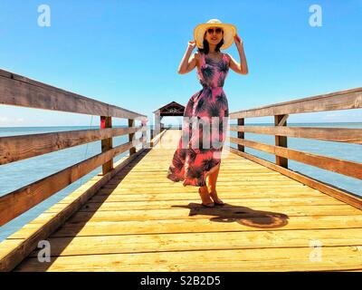 Beautiful young brunette woman with shapely figure, long floral pink and green sundress, pink sunglasses and sun hat smiling glowingly aboard a long fishing pier in tropical Waimea Kauai Hawaii. - Stock Photo