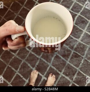 A red colorful glass mug being held by a woman standing onA checkered blue and white pattern Rug with bare feet and painted toenails - Stock Photo