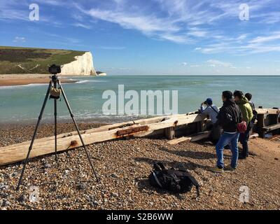 Tourists taking a picture of the Seven Sisters from Cuckmere Haven beach - Stock Photo
