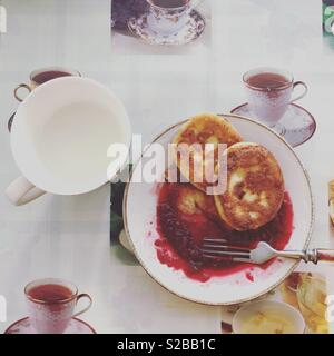 Cheese pancakes on the plate with a raspberry jam and a cup of milk on the table - Stock Photo