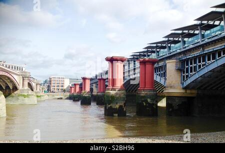 Three bridges at Blackfriars, showing the road/pedestrian bridge, the remaining supports for the old Victorian railway bridge and the new modern glass and steel rail bridge - Stock Photo