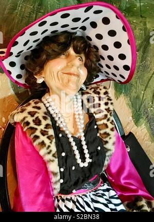 Mannequin of elderly woman sitting in black chair with black purse wearing black white and pink polka dotted hat, pink coat with faux leopard fur trim, pearl strands, black blouse  zebra print skirt - Stock Photo