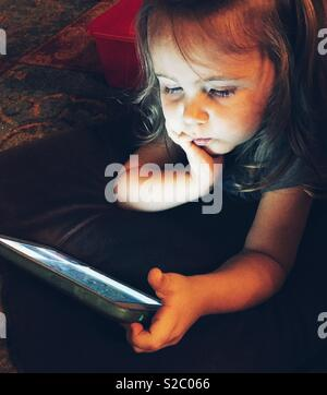 Toddler girl laying on floor in the dark playing with tablet - Stock Photo