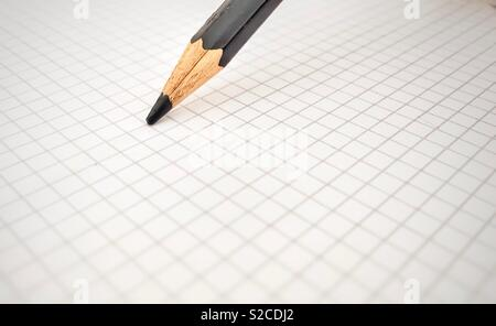 Black pencil on a blank squared sheet - Stock Photo