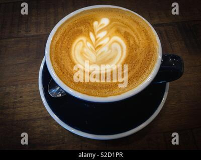 A cup of coffee latte. With a nice coffee art . For the best flavour and taste use freshly brewed coffee and full cream milk - Stock Photo