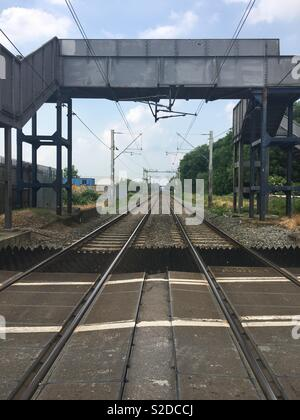 View along the train tracks from the middle of a level crossing, Waltham Cross, Cheshunt, UK - Stock Photo