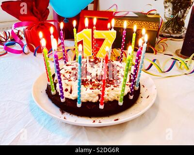 Birthday cake for a 17th birthday with burning candles and colorful decoration on a birthday table with presents in the background. - Stock Photo