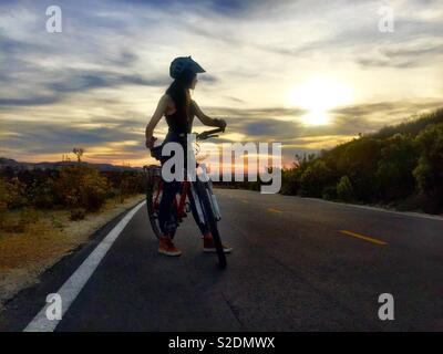 A teen girl riding a bike is silhouetted against a sunset in Southern California. - Stock Photo