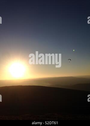 Sunset over hills with paraglider. - Stock Photo