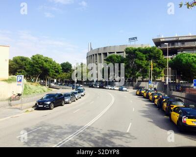 Taxis and cars parked in the street at the Camp Nou football stadium in Barcelona Spain - Stock Photo