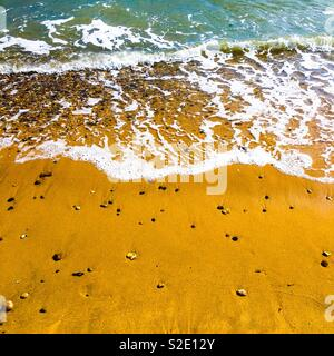 Waves washing onto a sandy beach, Westcliff-on-Sea, UK - Stock Photo