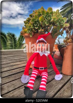 Naughty elf sitting on a table. - Stock Photo