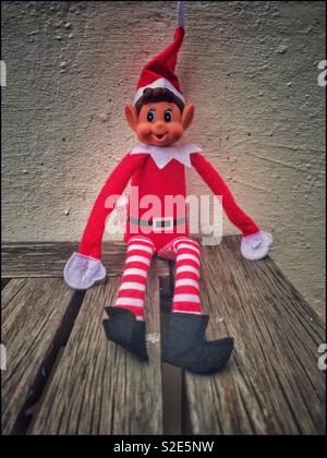 Naughty elf sitting on a wooden table. - Stock Photo
