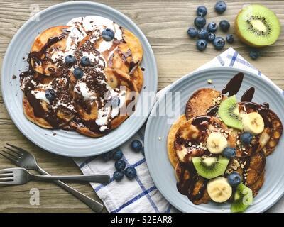 Vegan banana pancakes with chocolate syrup, kiwis, bananas and blueberries - Stock Photo