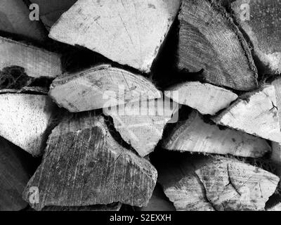 Pile of logs in wood store, black and white - Stock Photo