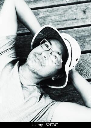 Middle aged Asian man wearing bucket hat and glasses looking up laying on camping platform in Canadian wilderness - Stock Photo