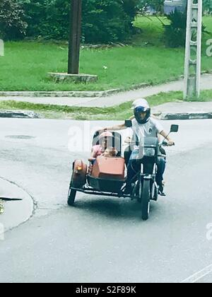 Family on a motorbike and sidecar nearly toppling over going around a corner in Havana Cuba - Stock Photo