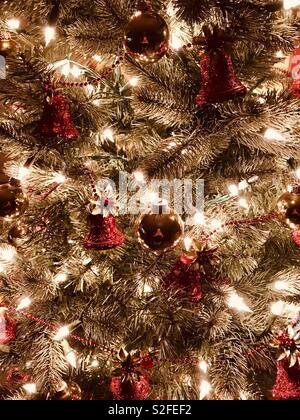 Green Christmas tree with white lights and gold and red shiny ornaments - Stock Photo